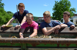 Students check temperature of compost and carbon in manure spreader